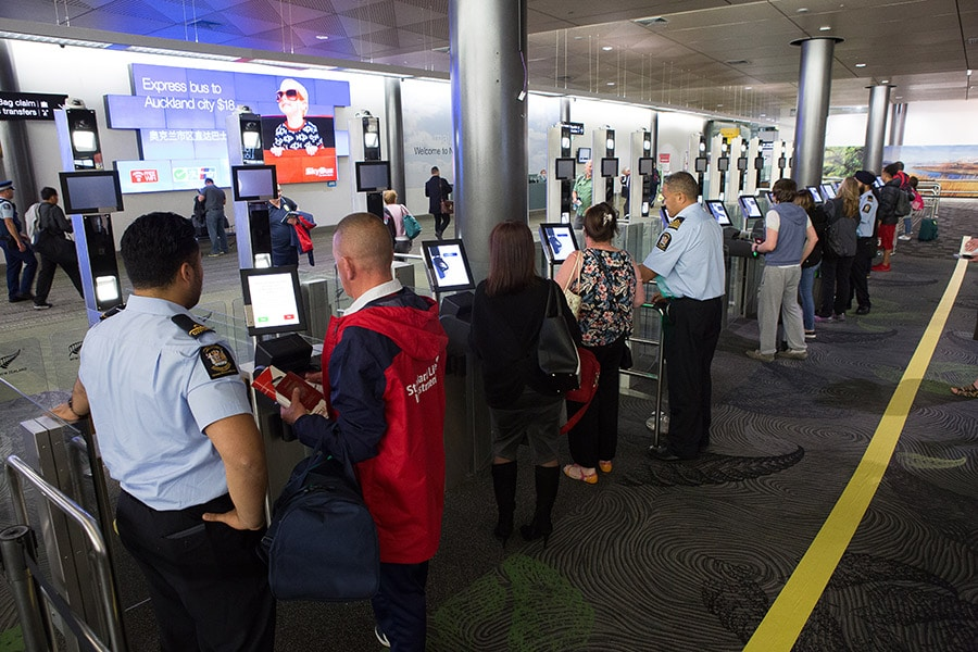 NZ Customs officers and passengers at self-service kiosks