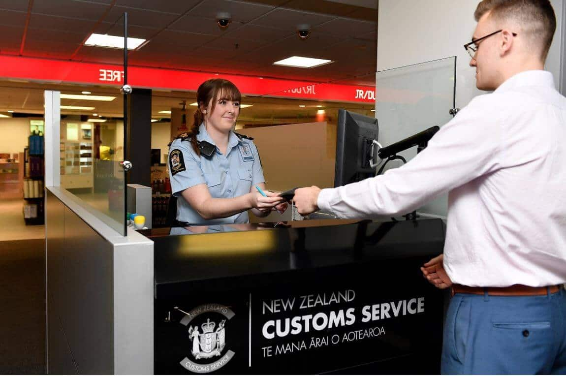 NZ Customs officer checking passenger's documents